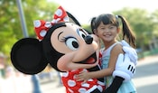 Minnie Mouse hugs a smiling young girl
