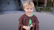 A young boy wears a Jedi robe and holds a toy lightsaber