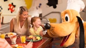 A smiling adult and child enjoying Character Dining with Pluto