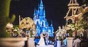 A bride and groom take their vows at night in front of Cinderella Castle at Walt Disney World Resort