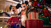 Mickey and Minnie dance on a holiday parade float
