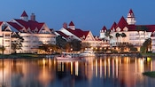 Boats travel the waterway in front of Disney's Grand Floridian Resort & Spa, lit up at nighttime