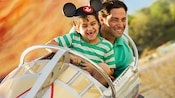 A father and his son, wearing a Mickey ear hat, have a blast on the Astro Orbiter