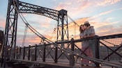 A couple relaxes on a bridge as the sun sets behind them
