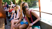 Passengers react with delight to the sites on a Jungle Cruise adventure