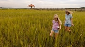 Mother and daughter trek through a field of marshy reeds, and in the background, a wooden walkway