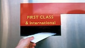 A hand dropping a letter into a First Class & International mail slot