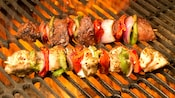 Skewers of meat and vegetables cooking on a grill