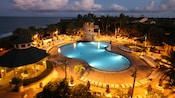 Evening lights illuminate the poolside area which features umbrellas, lounge chairs and a waterslide