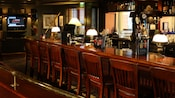 The old-fashioned bar, with wooden bar stools and counter, beer taps and a TV in the background