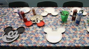 A decorating table with paint, paintbrushes and Mickey-shaped plates showcasing assorted designs