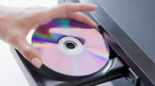 Close-up of a hand putting DVD into a DVD player