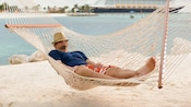 A man naps on a hammock with a Disney Cruise Line ship in the background