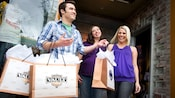 Two women smile at a man holding 3 shopping bags outside Disney Vault 28