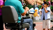 A Guest, seated on an ECV at Disneyland Park