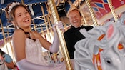 A young lady, in gown, gloves and tiara, rides the carousel during her Disneyland Quinceanera
