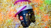 A refillable souvenir bucket featuring Main Street Electrical Parade-themed art sits in popcorn