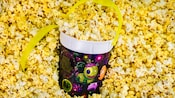 A refillable souvenir bucket featuring Disneyland's Summer Program art sits in popcorn