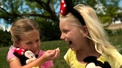 A girl holding a Minnie Mouse plush doll feeds popcorn to a girl wearing Minnie Ears