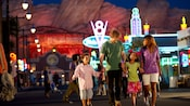 A family of four walks hand-in-hand through Cars Land in Disney California Adventure Park at night