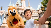 Pluto shakes a young boy's hand in front of Sleeping Beauty Castle