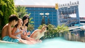 A family of 4 laughs while sitting on the ledge of a pool at the Disneyland Hotel