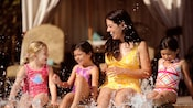 A smiling woman and 3 young girls sit at the edge of a pool and splash water around with their feet