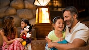 A young girl holding a plush Mickey chats with her mom while her sister chats with their dad in the lobby of their Disney Resort hotel