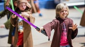 Young Guests wear youngling robes and hold light sabers during Jedi Training: Trials of the Temple
