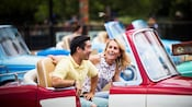 A couple sits inside a vehicle and enjoys the Luigi's Rollickin' Roadsters attraction