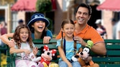 Smiling mom and dad behind young daughters seated on a park bench with Mickey and Minnie Mouse plush toys