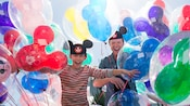 Smiling father and son with Mickey Mouse ear hats surrounded by Mickey Mouse balloons