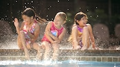 Three smiling young girls sit at the edge of a swimming pool and splash water around