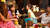 Two little girls sit with their mother and father in the lobby of their hotel and play with a Mickey plush toy