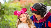 A young girl wearing a Minnie Mouse ears headband glances up as Snow White gives her a side hug