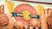 A 3D sign for 'Boudin Sourdough since 1849' surrounded by a variety of bread loaves