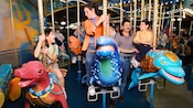 A family of 4 rides fanciful King Triton's Carousel sea creatures