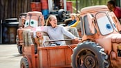 A mother and daughter laugh as they spin on Maters Junkyard Jamboree attraction