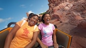 A happy mother and daughter ride the roller-coaster-like Big Thunder Mountain Railroad