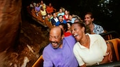 A man wraps his arm around his wife as the wild Big Thunder Mountain Railroad ride twists and turns