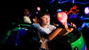 A little boy plays on the Buzz Lightyear Space Ranger Disneyland attraction