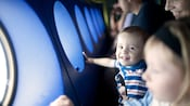 Along the Finding Nemo Submarine Voyage viewing portholes, a baby smiles at the camera