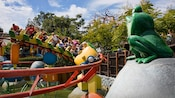 A silly frog statue sits and watches Guests on the gentle junior rollercoaster ride