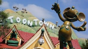 Travel around Toontown and see sights, like a Mickey Mouse statue and the Toontown sign