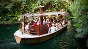 A Jungle Cruise boat drifts on waters that wind through the lush Adventureland landscape