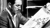 Old photo of Walt Disney, looking at an artist's sketch of Mickey Mouse in Steamboat Willie