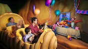 Guests roll past a birthday party on The Many Adventure of Winnie the Pooh attraction