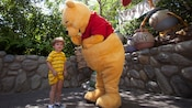 Winnie the Pooh shares a laugh with a young boy at Disneyland Park