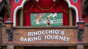 Above a wooden sign where the words Pinocchio's Daring Journey are painted between two lanterns, a balcony is styled as an ornately decorated marionette stage with a figure of Pinocchio posed as if performing