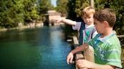 Two young boys lean against a wood fence; one points across the Rivers of America
